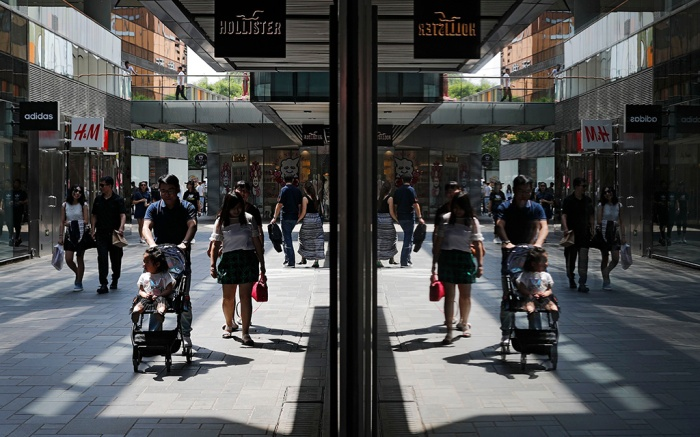 Shoppers are reflected on a window panel at an up-scale shopping mall in Beijing, . Growth in China's manufacturing sector slowed in April, official data showed Sunday, pointing to an unsteady recovery in the world's second-largest economyManufacturing, Beijing, China - 30 Apr 2017
