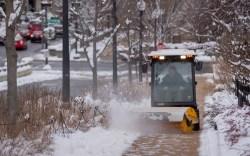 A worker clears a sidewalk of