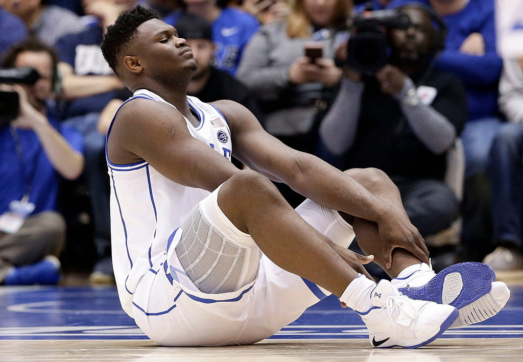 Duke's Zion Williamson sits on the floor following a injury during the first half of an NCAA college basketball game against North Carolina in Durham, N.CNorth Carolina Duke Basketball, Durham, USA - 20 Feb 2019