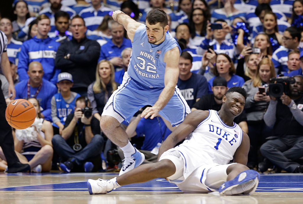 Zion Williamson, Luke Maye. Duke's Zion Williamson (1) falls to the floor with an injury while chasing the ball with North Carolina's Luke Maye (32) during the first half of an NCAA college basketball game in Durham, N.CNorth Carolina Duke Basketball, Durham, USA - 20 Feb 2019
