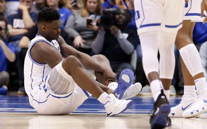 Duke's Zion Williamson sits on the floor following an injury during the first half of an NCAA college basketball game against North Carolina in Durham, N.CNorth Carolina Duke Basketball, Durham, USA - 20 Feb 2019