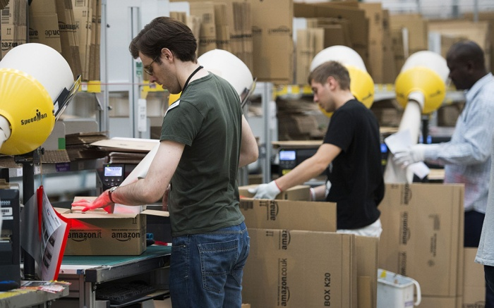 Amazon employees box packages at a warehouse