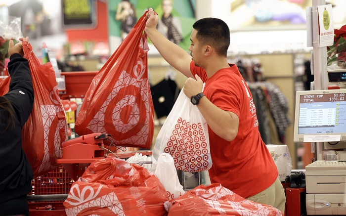 A Target employee hands bags to a customer at the register at a Target store in Colma, Calif. Target's fiscal fourth-quarter net income dipped 2 percent as it dealt with intense competition during the crucial holiday season. But its adjusted results beat analysts' estimates and it forecast first-quarter earnings above Wall Street's viewEarns Target, Colma, USA