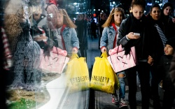 People carry shopping bags outside a