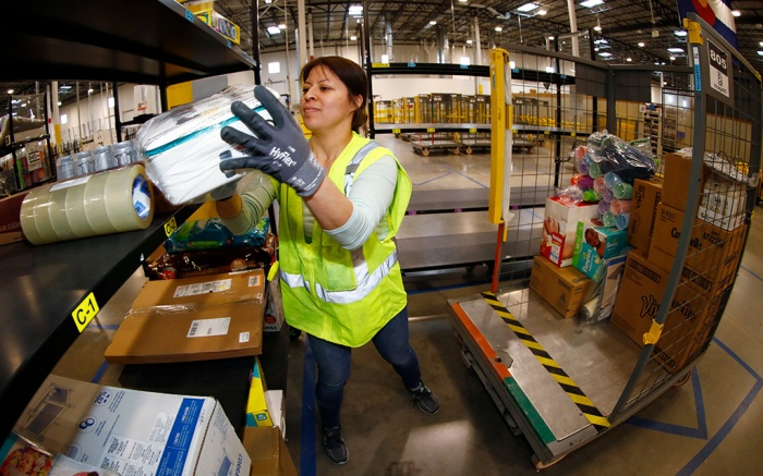 Amazon fulfillment center in Aurora, Colo. A worker moves an item from a cart to the line for boxing during a tour of the Amazon fulfillment center, in Aurora, Colo. More than 1,000 full-time associates work in the Aurora facility, which opened in September 2017, and is one of more than 100 such fulfillment centers scattered across North AmericaAmazon Colorado, Aurora, USA - 03 May 2018