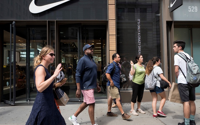 People pass a Nike store in New York, . An endorsement deal between Nike and Colin Kaepernick is prompting a flood of debate online as sports fans react to the apparel giant backing an athlete known mainly for starting a wave of protests among NFL players of police brutality, racial inequality and other social issuesKaepernick Nike, New York, USA - 04 Sep 2018