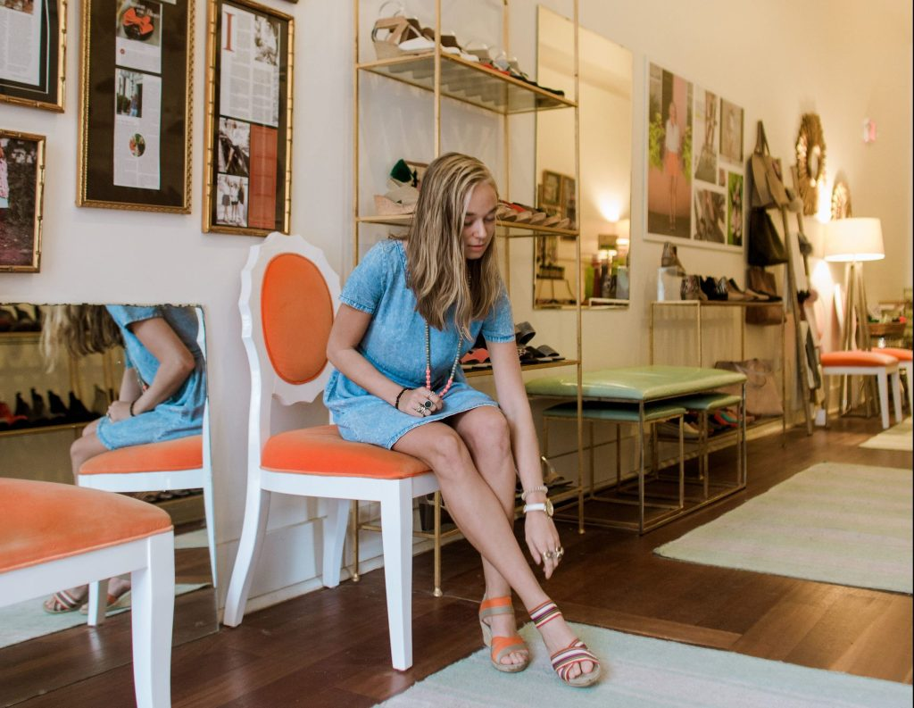 A woman tries on a pair of Charleston Shoe Co. shoes inside one of their stores.