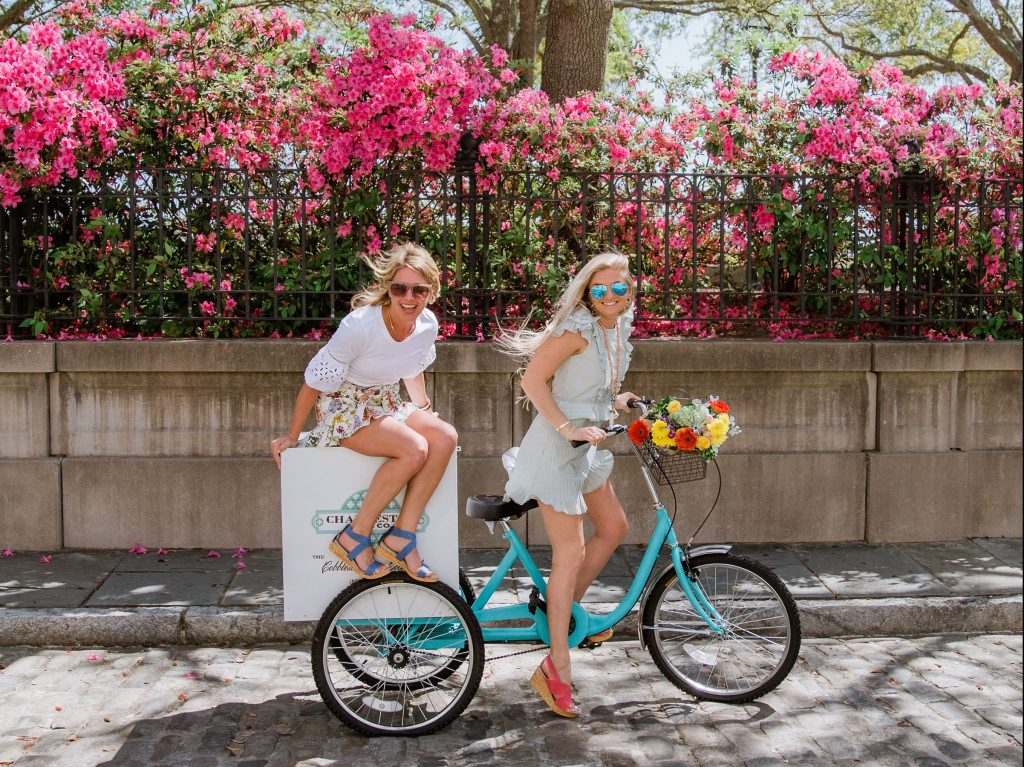 Two girls ride a bike in Charleston Shoe Co shoes