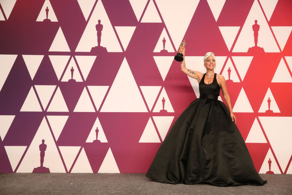 Lady Gaga with her Oscar in a Brandon Maxwell gown and Giuseppe Zanotti platform boots underneath.