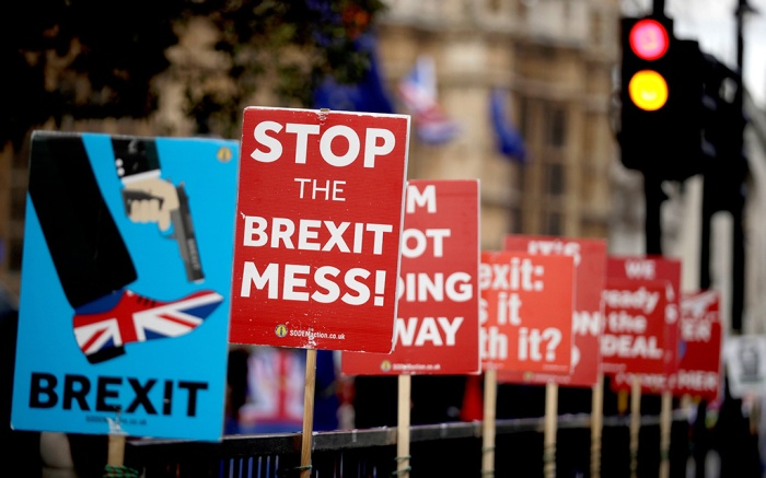 Placards placed by anti-Brexit supporters stand opposite the Houses of Parliament in London, . British Prime Minister Theresa May was making a last-minute push Monday to win support for her European Union divorce deal, warning opponents that failure to approve it would mean a long ? and possibly indefinite ? delay to Brexit. Parliament has rejected the agreement twice, but May aims to try a third time this week if she can persuade enough lawmakers to change their mindsBrexit, London, United Kingdom - 18 Mar 2019