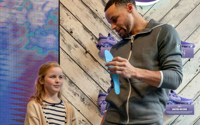 Nine-year-old Riley Morrison takes a look at the sockliner she designed for Stephen Curry's latest sneaker, the UA ICON Curry 6 United We Win