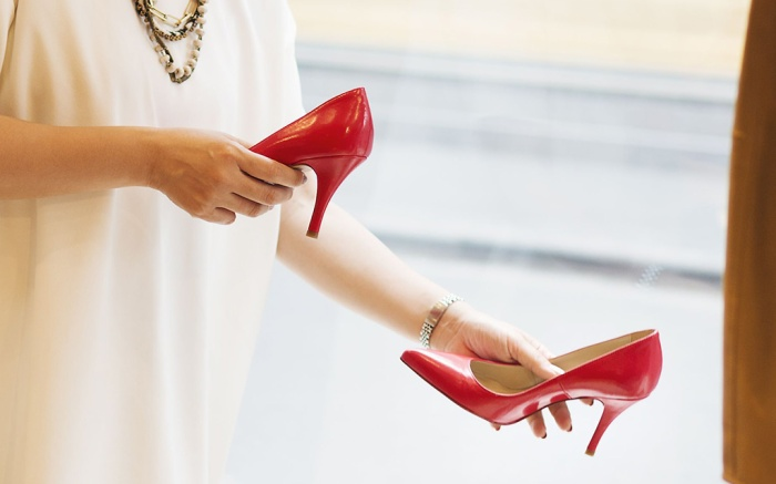 small red shoes, MODEL RELEASED Woman working in a fashion boutique in Tokyo, Japan, holding a pair of red high heels.VARIOUS