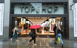 Shoppers walk by a Topshop store