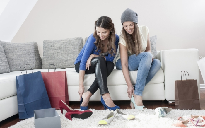 MODEL RELEASED Two young female friends sitting side by side on couch at home trying on high heelsVARIOUS
