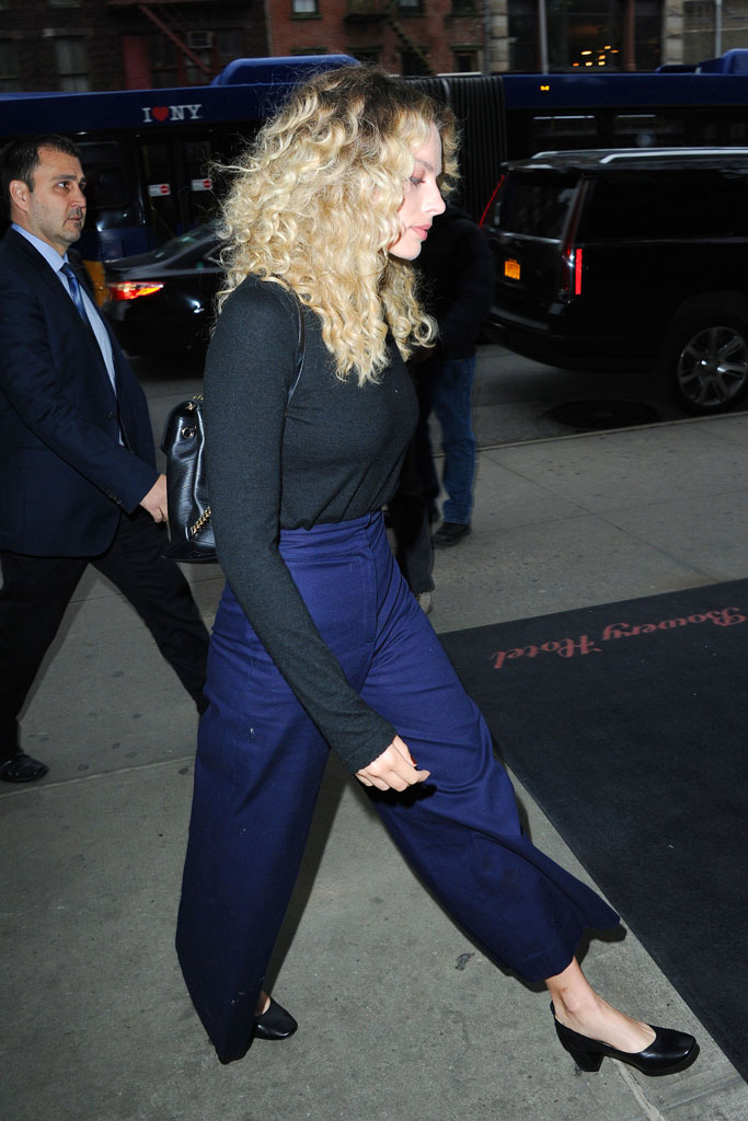 Margot Robbie, celebrity style, curly blond hair, black block-heeled pumps, blue flare-legged pants