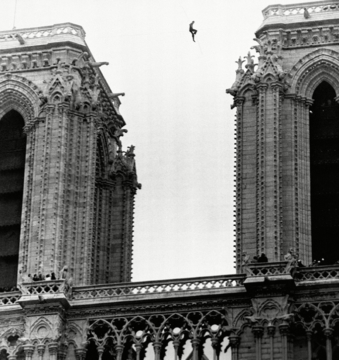 Philippe Petit, a 21-year-old professional tightrope walker, appears as the tiny figure sitting on a tightrope, strung 225 feet above the ground,between the two towers of Notre Dame cathedral, Paris,, during a stunt which lasted several hours, with police unable to bring him downParis Philippe Petit, Paris, France