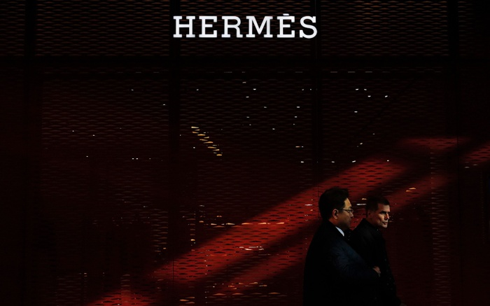A Chinese and foreign businessmen walk by an Hermes flagship store at the Central Business District in Beijing, . China will bar government authorities from demanding overseas companies hand over technology secrets in exchange for market share, a top economic official said Wednesday, addressing a key complaint at the heart of the current China-U.S. trade disputeForeign Investment, Beijing, China - 06 Mar 2019