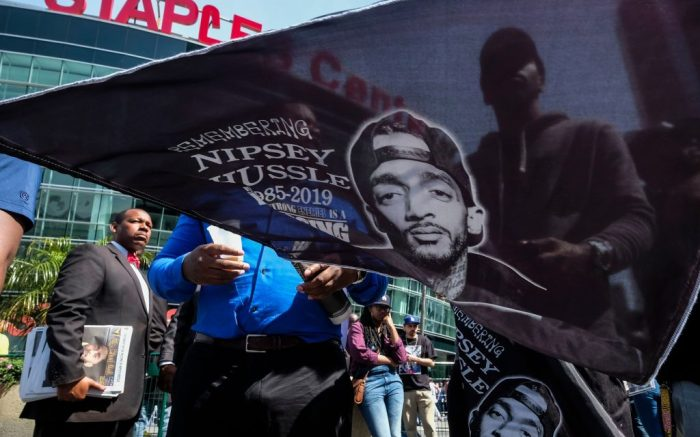 A fan of rapper Nipsey Hussle holds a flag with Hussle's image on it as he attends a public memorial at Staples Center in Los Angeles, . Hussle was killed in a shooting outside his Marathon Clothing store in south Los Angeles on March 31Obit Nipsey Hussle, Los Angeles, USA - 11 Apr 2019