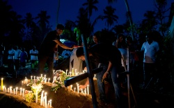 Relatives light candles after the burial