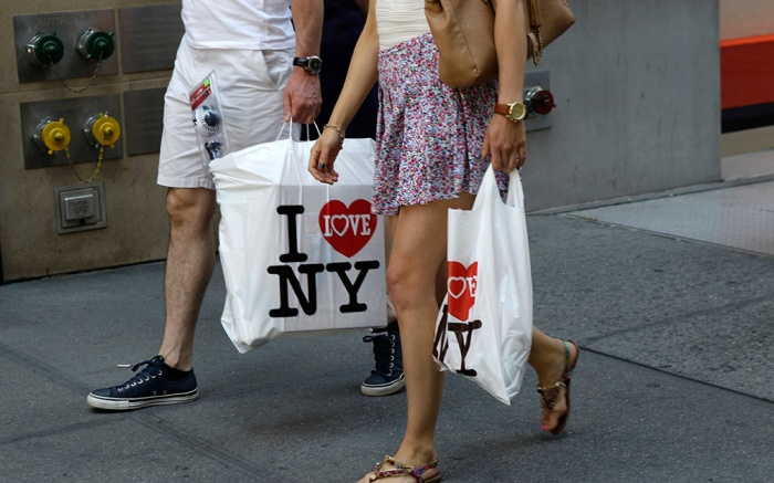 A couple walk with shopping bags on the sidewalk along Fifth Avenue in New York. Hot weather and clearance sales drew Americans into stores in July, giving retailers solid sales gains and helping offset worries about jobs and the economyChain Store Earns, New York, USA