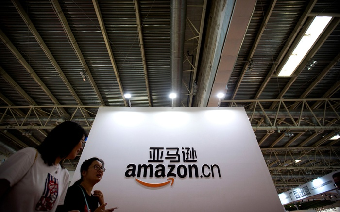 Visitors walk past a logo for Amazon China at the Beijing International Book Fair in Beijing, . The fair, which draws Chinese and international publishers, runs until Aug. 27Book Fair, Beijing, China - 23 Aug 2017