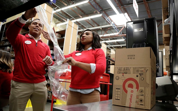 Employees demonstrate how air pillow machines work at a packaging station in the backroom of a Target store in Edison, N.J. The backroom of the Target store in Edison, N.J. is one of 133 stores that Target has dramatically overhauled to speed up shipping online orders from stores. Workers have new apps and tools to make their jobs easier, while their tasks are now divided into four key roles; picker, prepper, packer and sorter. New equipment like conveyor belts, redesigned air pillow machines and new carts that help organize orders shave off seconds in assembling the orders to online customersEarns Target, Edison, USA - 16 Nov 2018