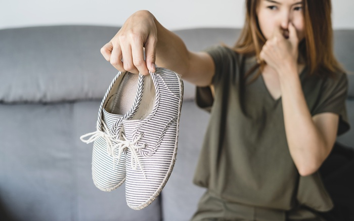 Young asian woman holding a pair of smelly and stinky shoes at home; Shutterstock ID 1006919044