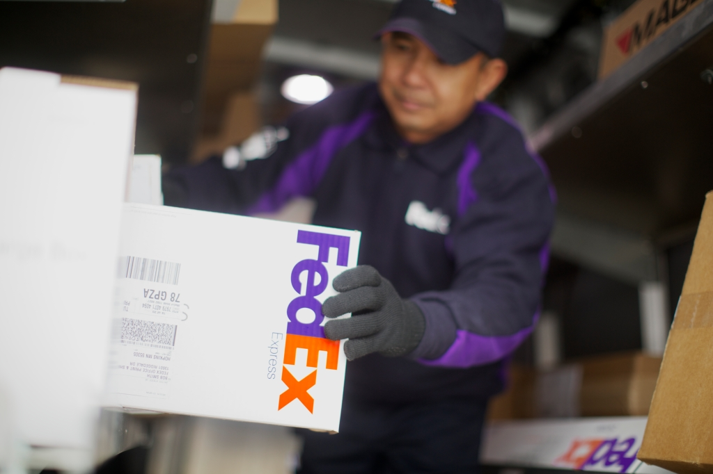 Fedex employee holding Fedex package