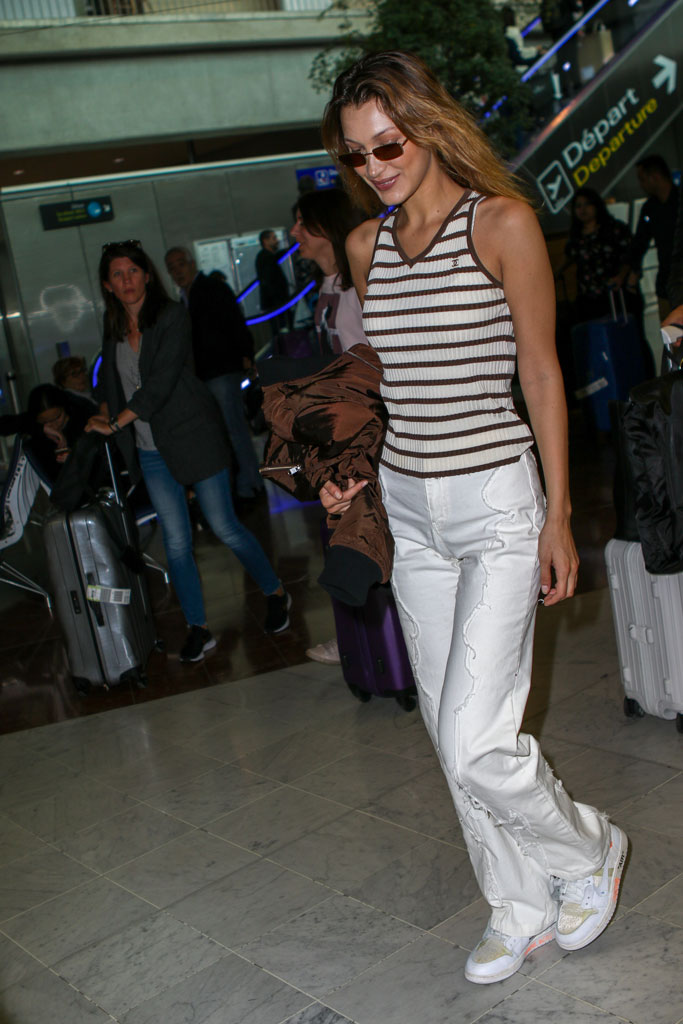 Bella Hadid, nice airport, celebrity style, striped chanel ribbed tank top, distressed pants, off-white x nike sneakers, celeb style