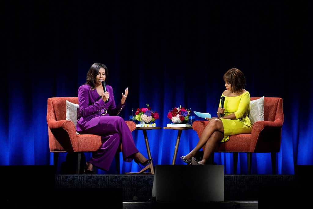 """Michelle Obama, sergio hudson pantsuit, purple suit, black pumps, Gayle King. Former First Lady Michelle Obama attends An Intimate Conversation about her book 'Becoming: with Michelle Obama', featuring moderator Gayle King at State Farm Arena, in Atlanta""""Becoming: An Intimate Conversation with Michelle Obama"""" - , Atlanta, USA - 11 May 2019"""