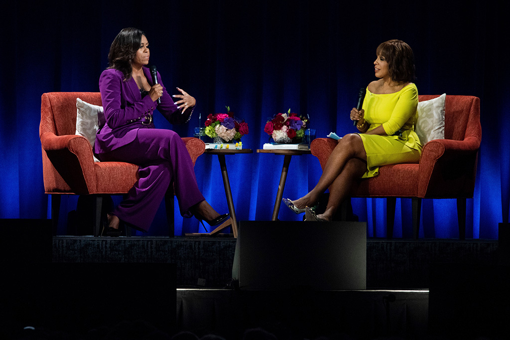 """Michelle Obama, purple pantsuit, sergio hudson suit, celebrity style, classic black pumps, Gayle King. Former First Lady Michelle Obama attends An Intimate Conversation about her book 'Becoming: with Michelle Obama', featuring moderator Gayle King at State Farm Arena, in Atlanta""""Becoming: An Intimate Conversation with Michelle Obama"""" - , Atlanta, USA - 11 May 2019"""