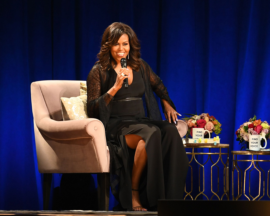 Former First Lady Michelle Obama'Becoming' book tour, Florida, USA - 10 May 2019, plunging black jumpsuit, ankle strap sandals