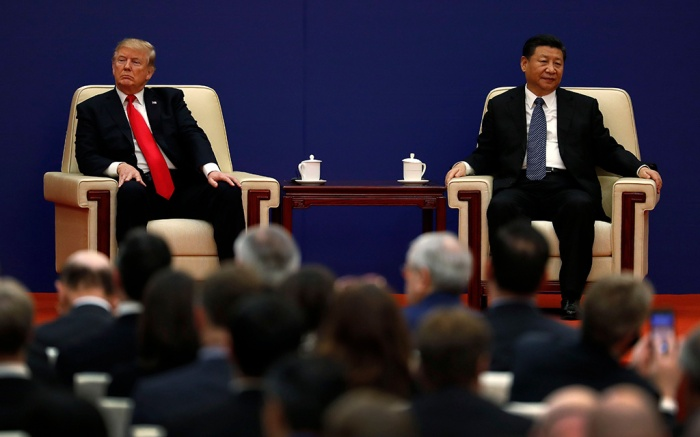 Donald Trump, Xi Jinping. U.S. President Donald Trump, left, sits next to Chinese President Xi Jinping during a business event at the Great Hall of the People in Beijing. The brewing China-U.S. trade conflict features two leaders who've expressed friendship but are equally determined to pursue their nation's interests and their own political agendas. But while Trump faces continuing churn in his administration and a tough challenge in midterm congressional elections, Xi leads an outwardly stable authoritarian regime. Xi recently succeeded in pushing through a constitutional reform allowing him to rule for as long as he wishes while facing no serious electoral challenge.owing him to rule for as long as he wishes without facing serious electoral challengesUS Xi vs Trump, Beijing, China - 09 Nov 2017