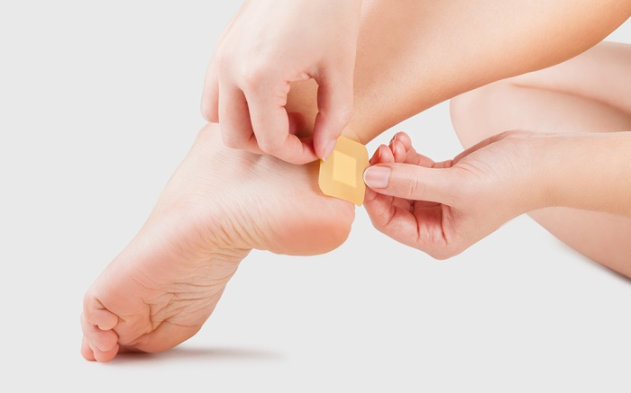 Closeupbest-blister-prevention-treatment of woman's heel with blister plaster on. Patch on the blister on the leg. First aid; Shutterstock ID 1220179339