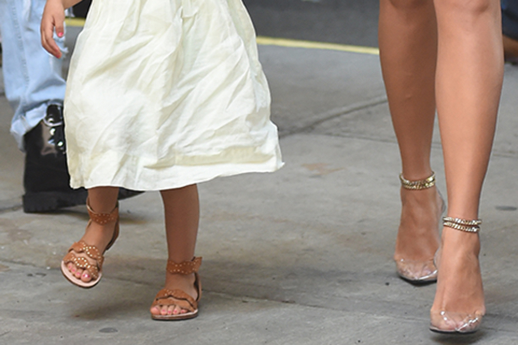 A close up of Chrissy Teigen and daughter Luna Stephens shoes, gladiator sandals, clear sandals, toddler shoes, pvc shoes, spring 2019 trends