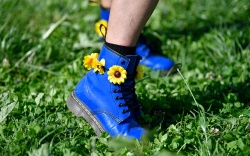 A festival goer shows her boots