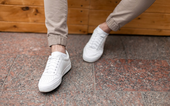 Men's legs in leather fashion white sneakers in stylish beige pants. Trendy casual outfit. Details of everyday look. Street fashion. Close-up.; Shutterstock ID 1381540880; Usage (Print, Web, Both): Web; Issue Date: 6/20