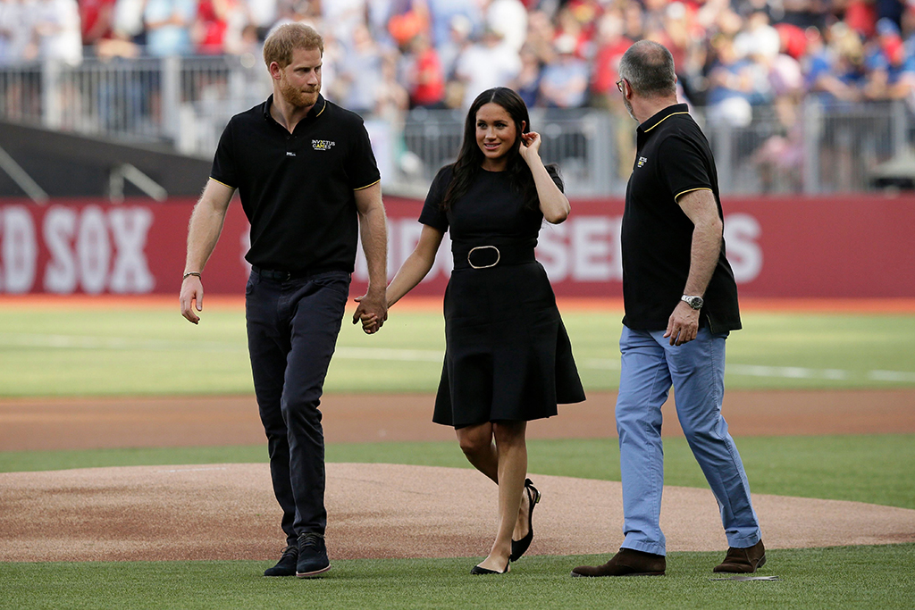 Britain's Prince Harry, left, and Meghan, Duchess of Sussex, walk off the field before a baseball game between the Boston Red Sox and the New York Yankees, in London. Major League Baseball makes its European debut game today at London StadiumRed Sox Yankees Baseball, London, United Kingdom - 29 Jun 2019