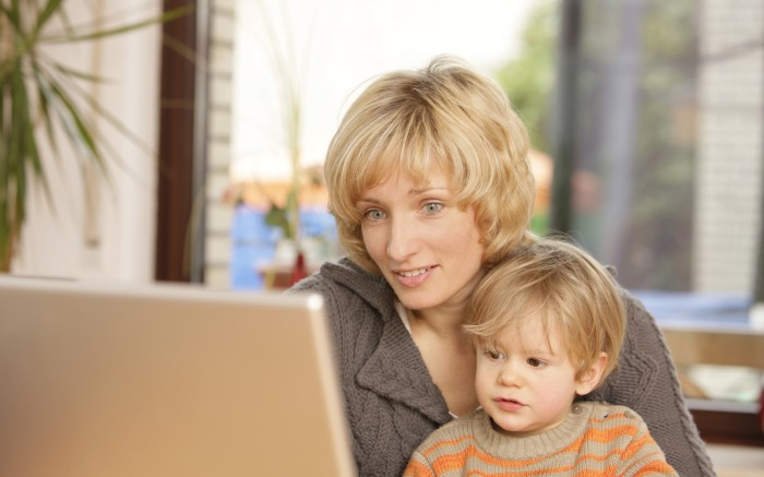 MODEL RELEASED Blonde mother with 2 year old son at the laptopVARIOUS