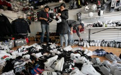 Shoppers holding shoes, a pile of