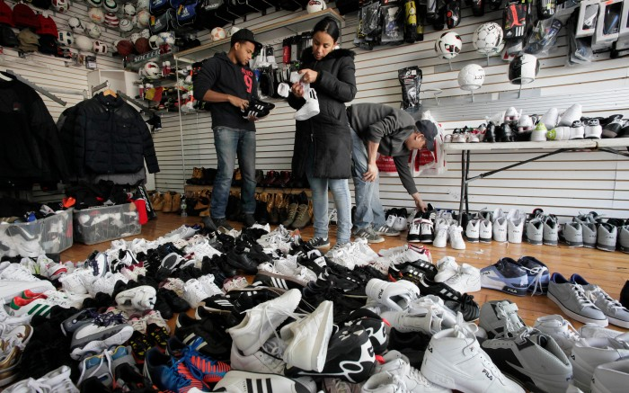 Shoppers holding shoes, a pile of shoes in the foreground