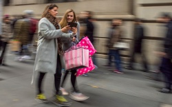 Shoppers carry their purchases as they