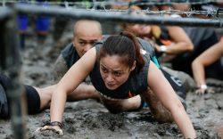 A participant crawls through mud under