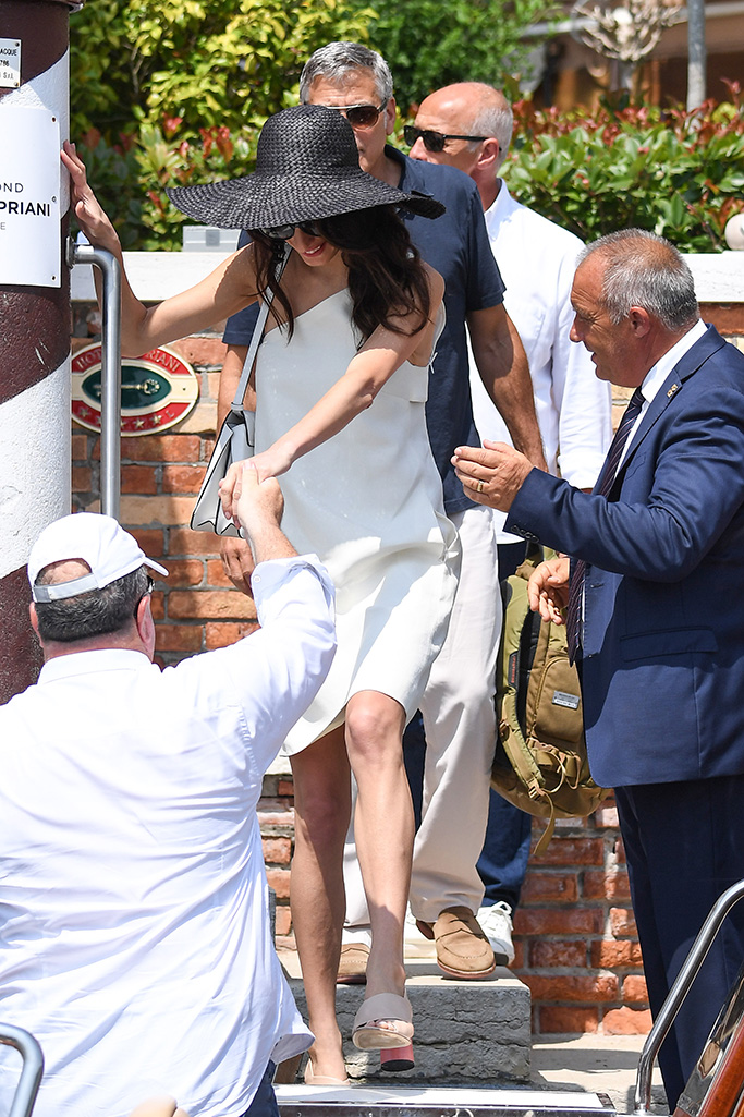 Amal Clooney, white one-shoulder dress, black hat, beige sandals pink round cylinder heel, george clooney