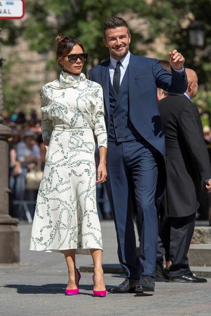 victoria beckham, fall 2019 dress, hot pink pumps, celebrity shoe style, Former English soccer player David Beckham (R) and his wife Victoria Beckham (L) arrive at Sevilla's cathedral to attend the wedding between Spanish Real Madrid soccer player Sergio Ramos and Pilar Rubio, in Sevilla, southern Spain, 15 June 2019.Wedding of Sergio Ramos and Pilar Rubio, Sevilla, Spain - 15 Jun 2019