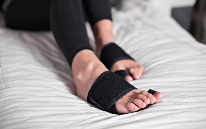 Woman foot bunion protection. Bunion corrector. lifestyles photos in bed, on floor. different angels. ; Shutterstock ID 1304797726; Usage (Print, Web, Both): Web; Issue Date: 7/22best-bunion-splint-correctors
