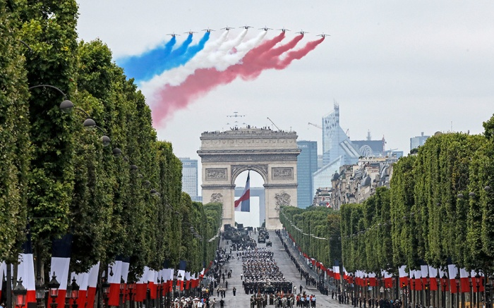 French Alpha jets of the Patrouille de France spray lines of smoke in the colors of the French flag over the Champs-Elysees avenue during the Bastille Day parade in Paris, FranceBastille Day, Paris, France - 14 Jul 2019