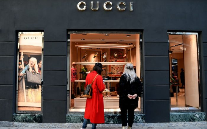 Shoppers looking through the windows of a Gucci store.Gucci store, Copenhagen, Denmark - 14 Sep 2018