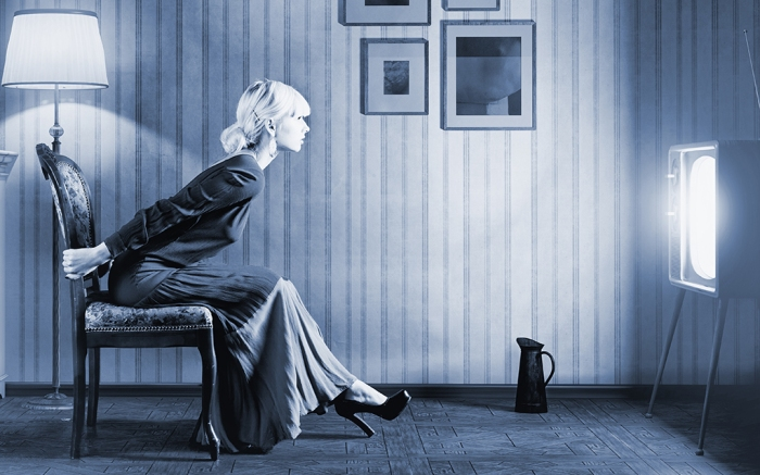 Young  woman sitting on a chair in vintage interior  and watching retro tv. She is very astonished while watching tv in dark room ; Shutterstock ID 146949626; Usage (Print, Web, Both): Web feature; Issue Date: 07/03; Comments: Tv advertising