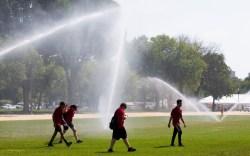 Youths walk under large sprinklers on